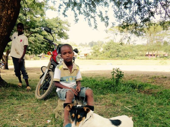 A young Tanzanian boy waiting with his dog at FVAI clinic in Baraa Tanzania