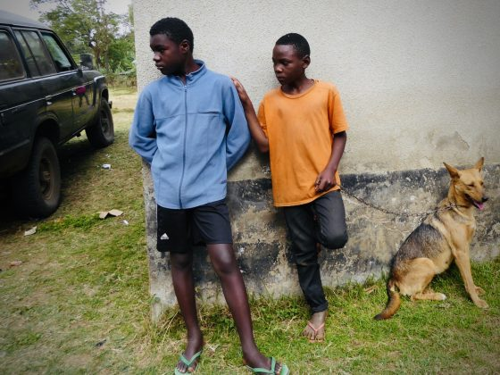 Two young men waiting with their dog at spay neuter clinic in Tanzania