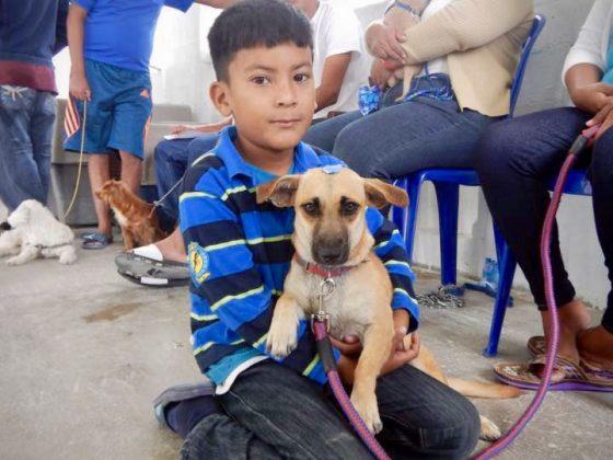 Un jeune belizien et son chien à Sarteneja, Belize