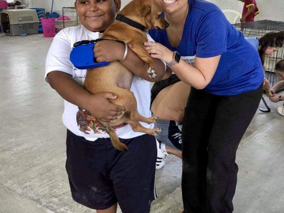 Une bénévole FAVI accueille un enfant et son chien à la clinique.